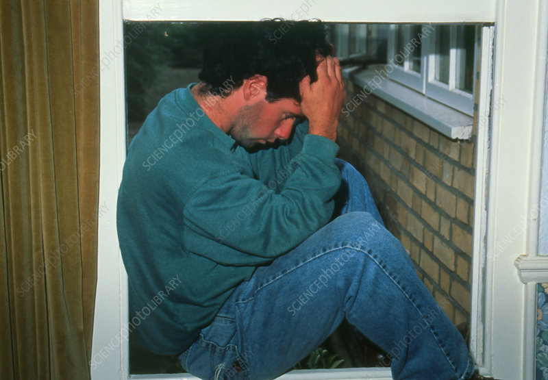 Depressed young man sits dejected at window