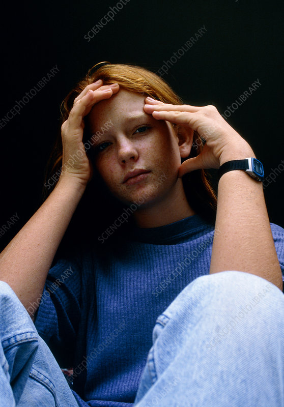 Depressed teenage girl holding her head