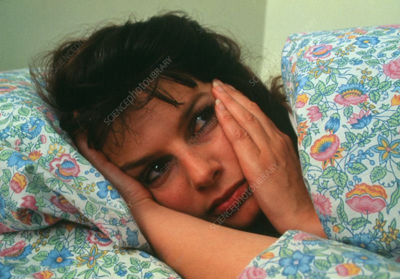 Depressed or sad woman lying in bed
