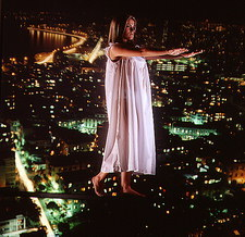 Abstract image of sleepwalking woman above a city