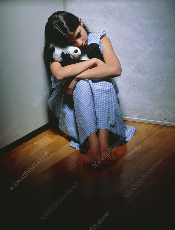 Depressed young girl sitting in corner of room