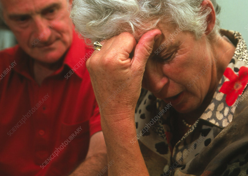 Depressed elderly woman with partner looking on