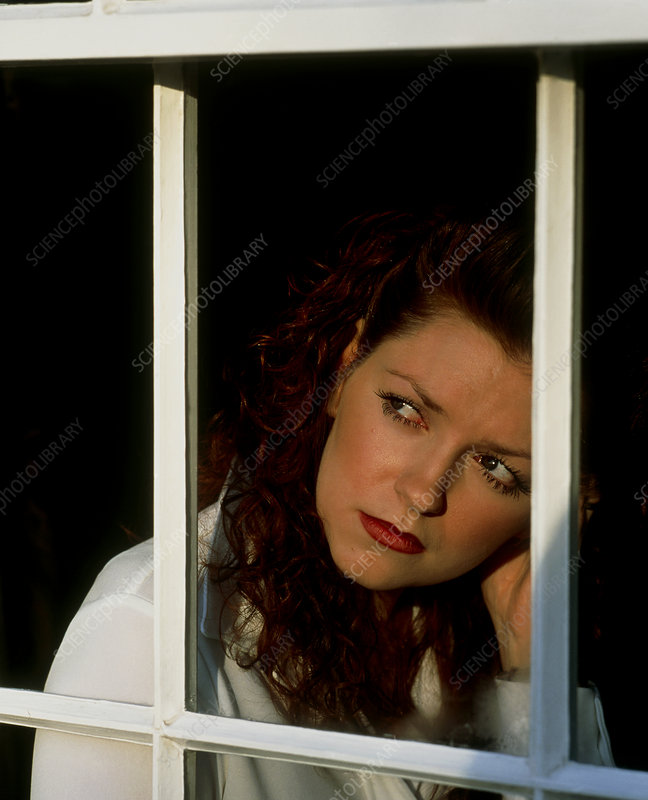 A depressed young woman stares out of a window