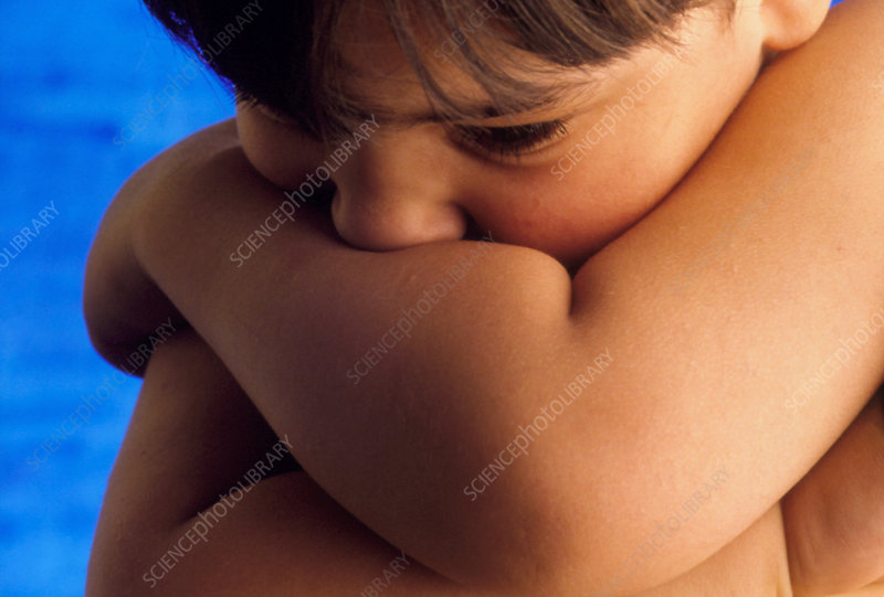 4 year old autistic boy hugging bare arms to chest