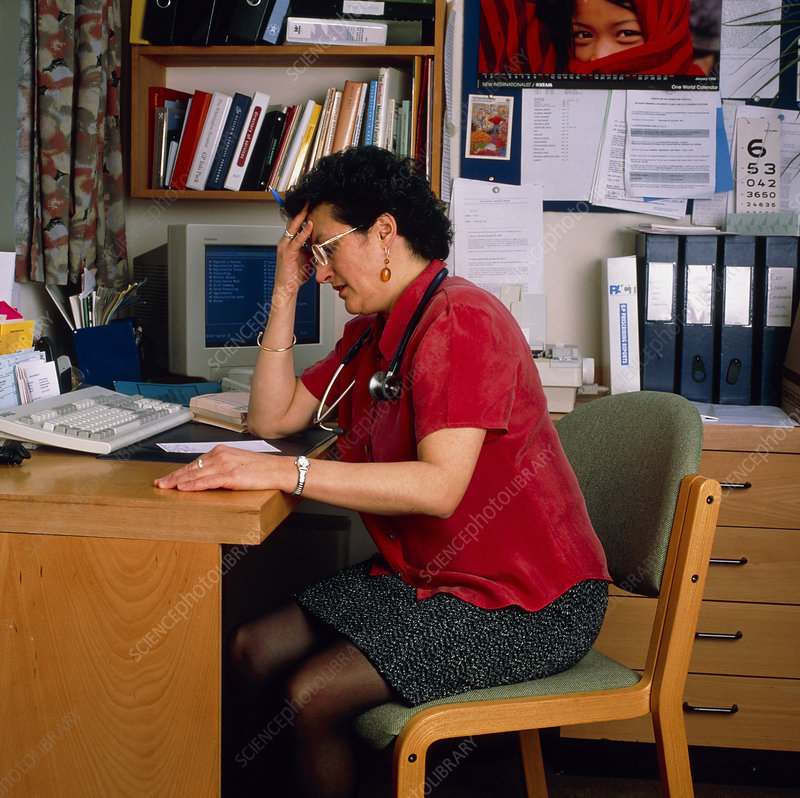 Stressed female GP doctor working at her desk