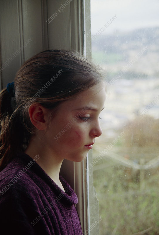 Depressed girl looking out of a window