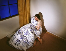 Fearful woman clutching a duvet in a corner