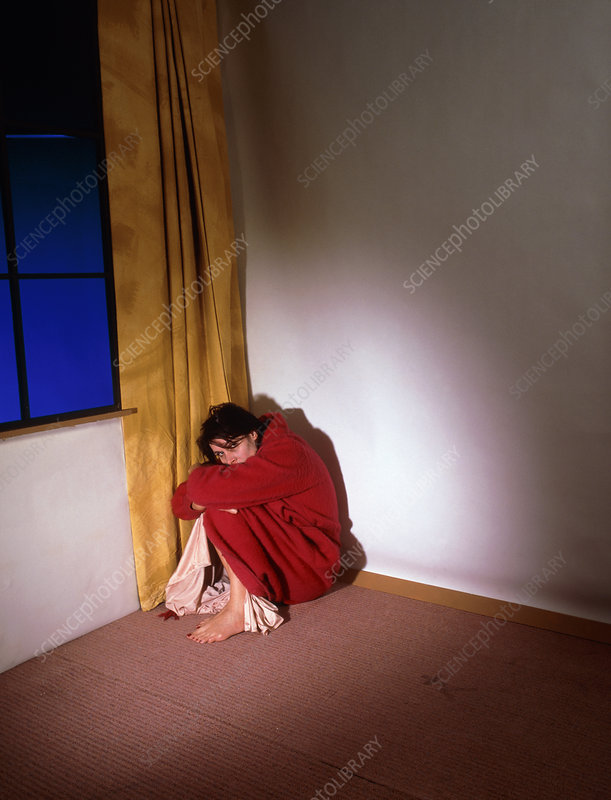 Depressed woman crouched in the corner of a room
