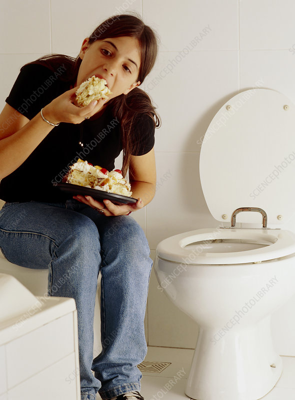 Bulimia: young woman eats alone at a toilet