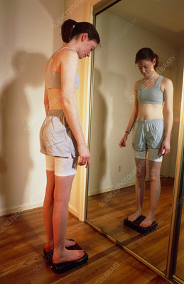 View of an anorexic woman looking in a mirror