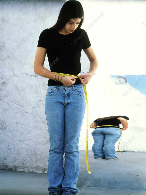 Anorexic teenage girl measuring herself with tape