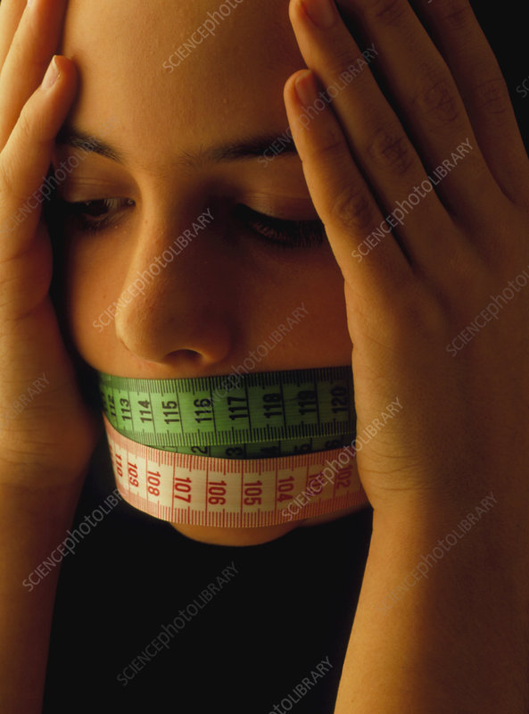 Teenage girl with tape measures over her mouth