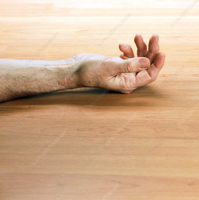 Man's arm laying on a floor