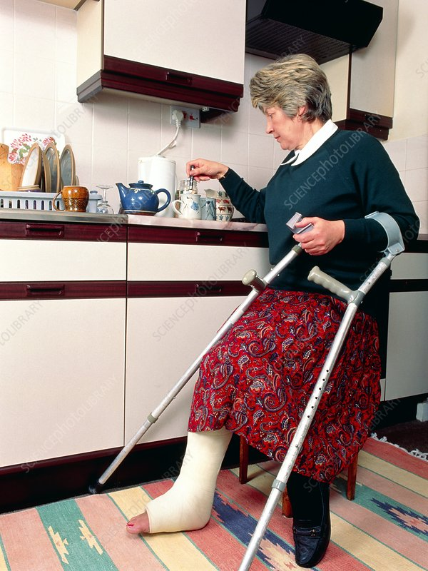 Woman with broken leg and crutches makes tea