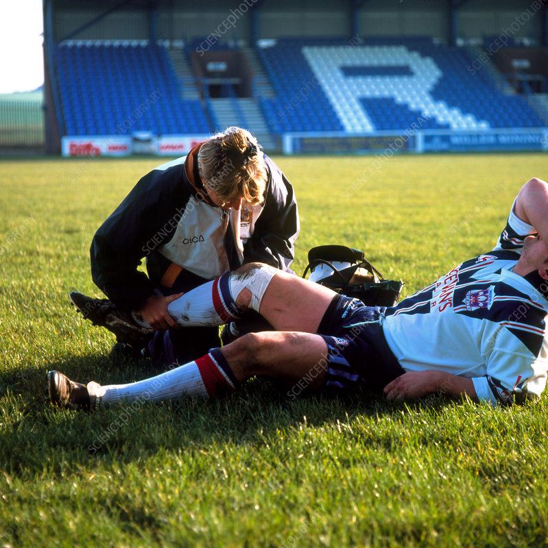 Physiotherapist examining player's injured knee