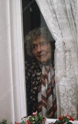 Elderly lady peering out of house window