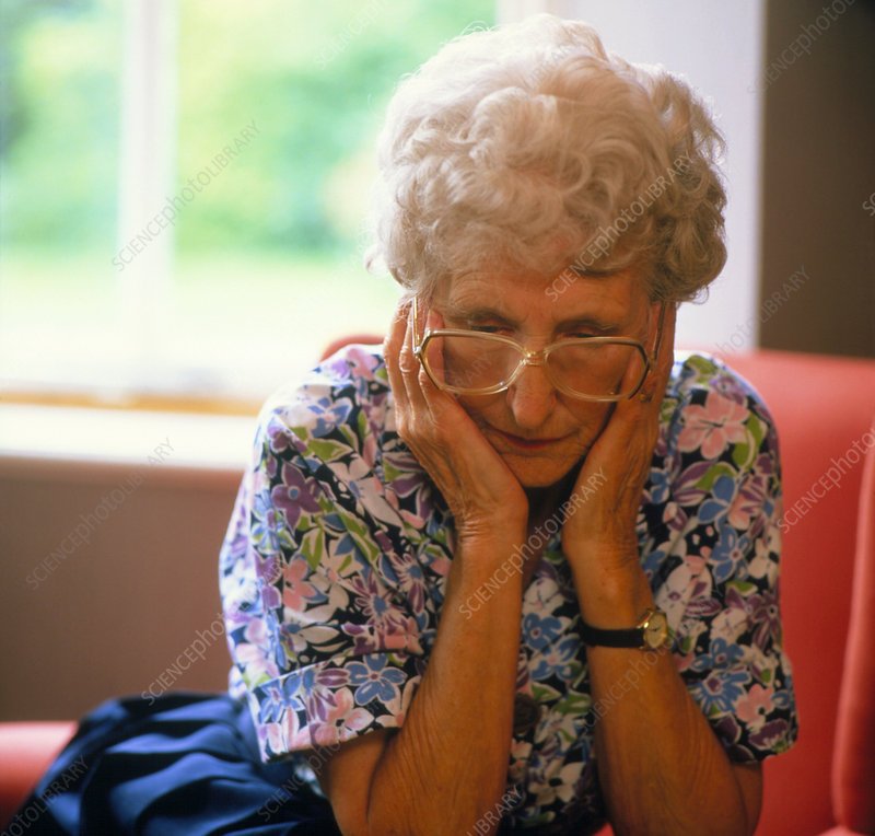Loneliness: elderly woman clasping face in hands