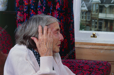 Loneliness: elderly woman staring out of window - Stock ...