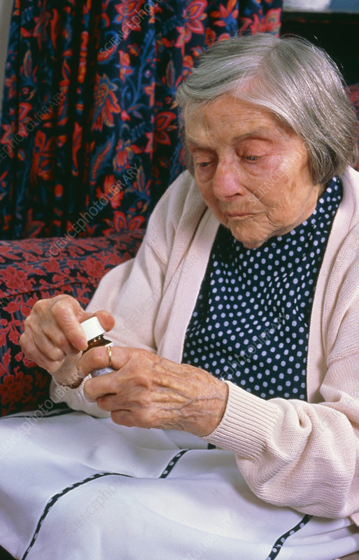 Elderly woman with bottle of tablets
