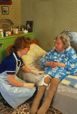 Elderly woman with incontinence bag, and nurse