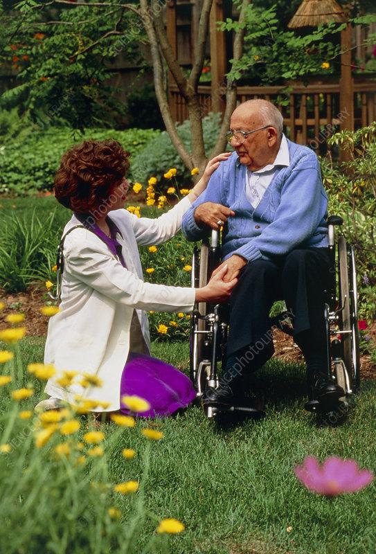 Disabled elderly man receiving home visit