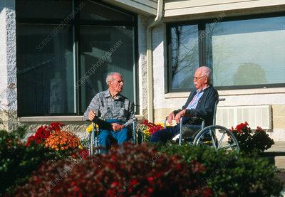 Elderly men in wheelchairs outside nursing home