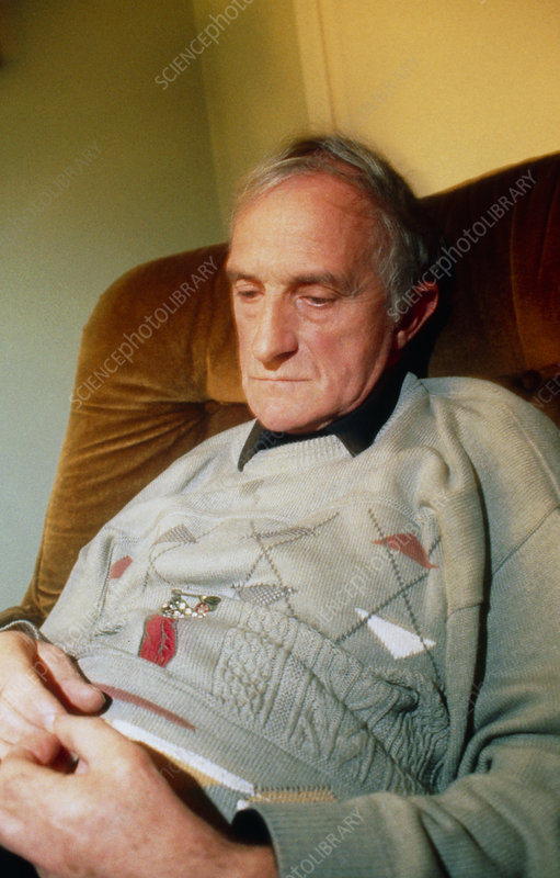 Elderly man sits depressed and lonely