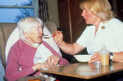 Nurse feeds elderly woman suffering from arthritis