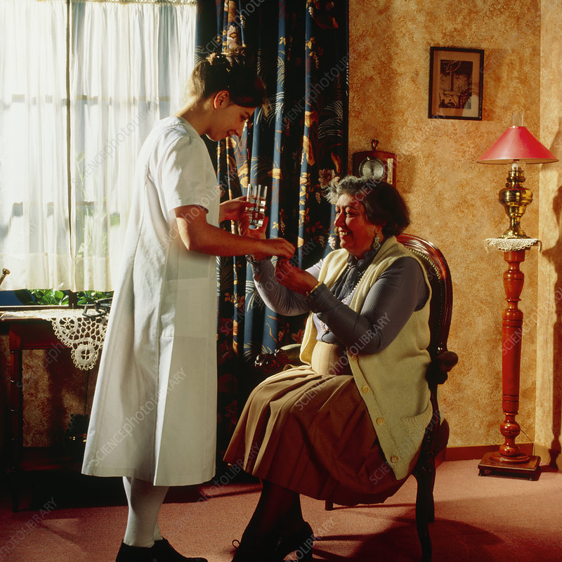 Nurse gives elderly woman her medication at home