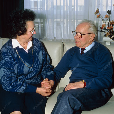 Elderly couple hold hands lovingly at home