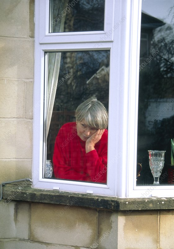 Depressed elderly woman stares through a window
