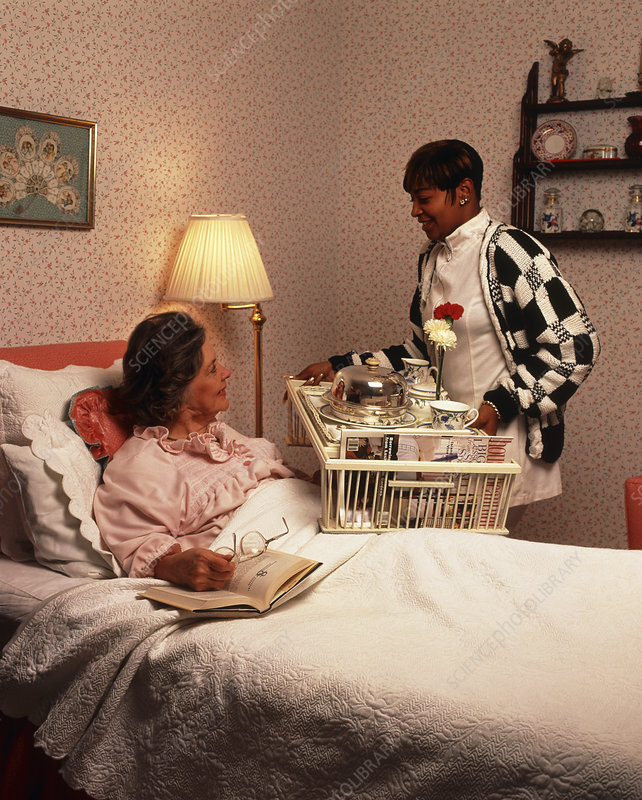 Home help gives elderly woman breakfast in bed