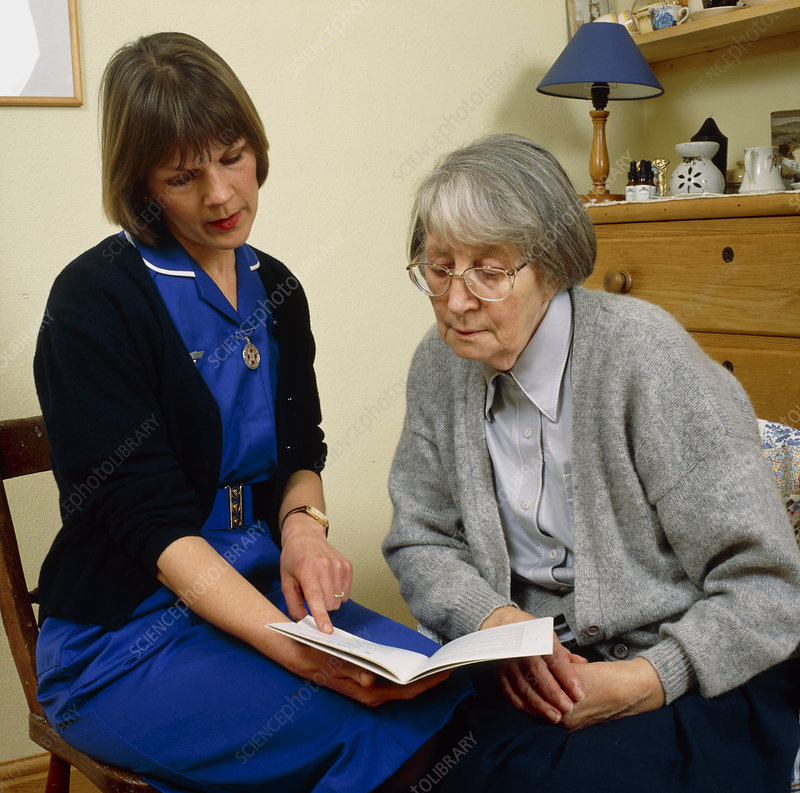 District nurse shows information book to old woman