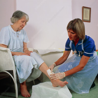 District nurse bandages leg ulcer on old woman