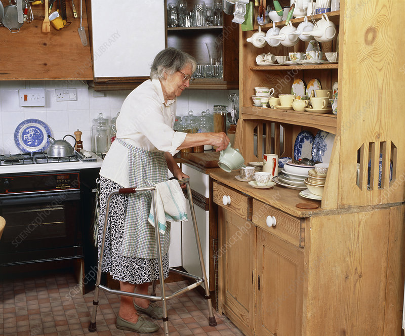 Elderly woman with zimmer frame makes cup of tea