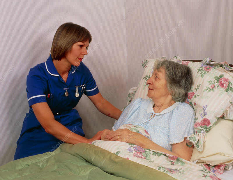District nurse talks to elderly bedridden patient