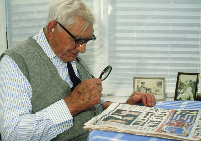 Elderly man uses a magnifying glass to read paper