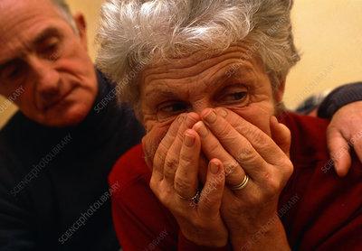 Upset elderly woman comforted by elderly man