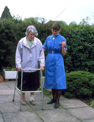 District nurse helps old woman use walking frame