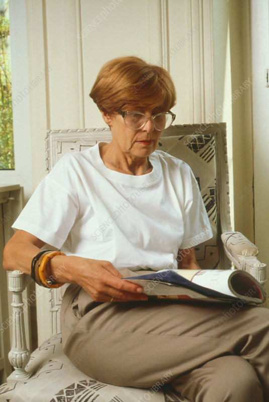 Elderly woman sitting reading in an old age home