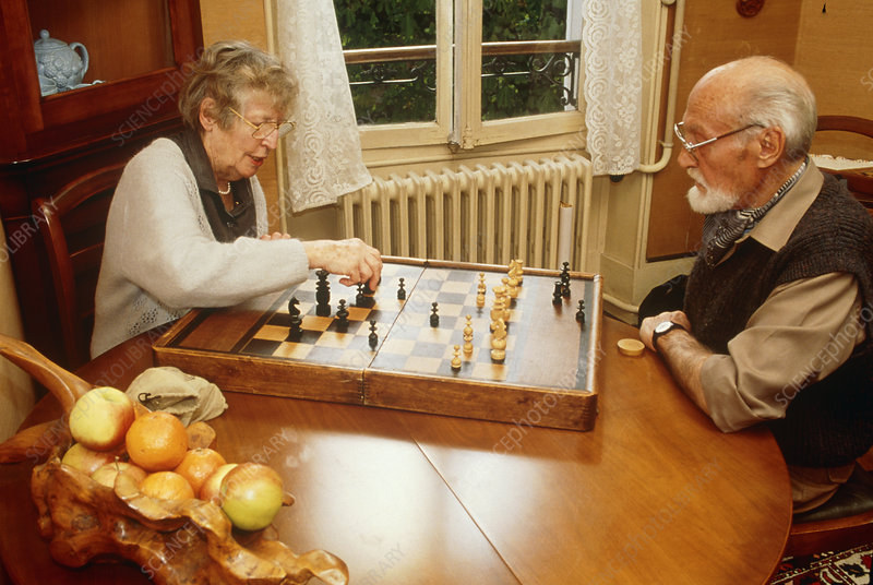 Elderly couple playing chess in an old age home