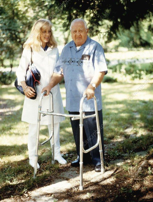 Nurse assisting an elderly man in a walking frame