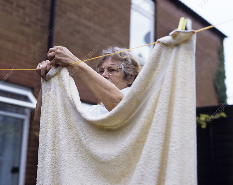 Elderly woman hanging washing
