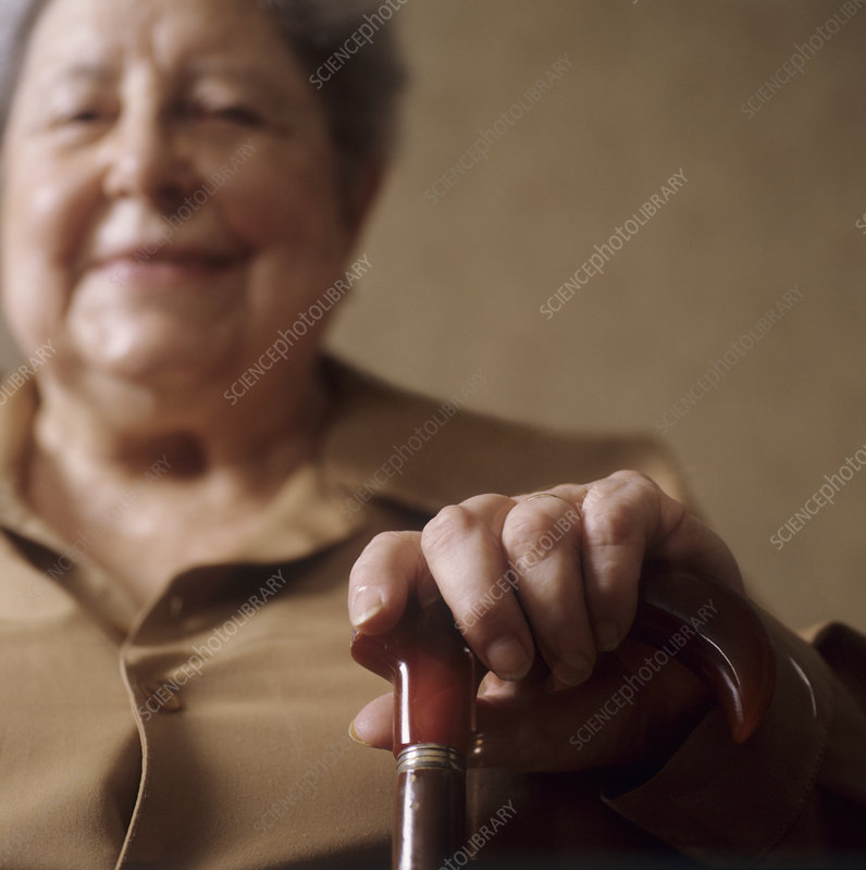 Elderly woman clasping a walking stick