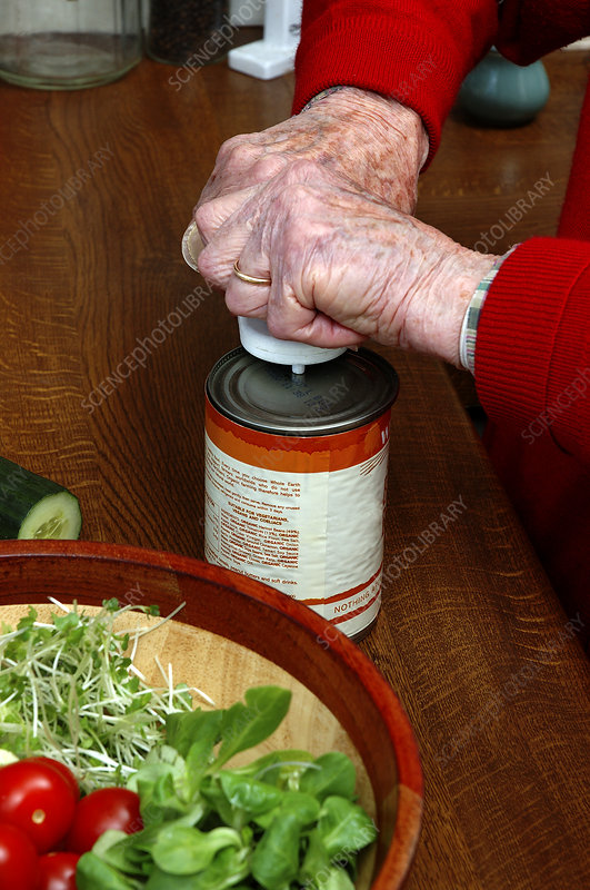 Elderly person opening a can of food