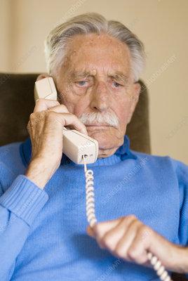 Elderly man using a telephone