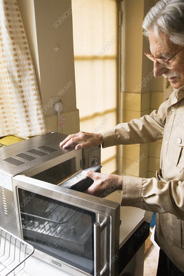 Elderly man using a microwave oven