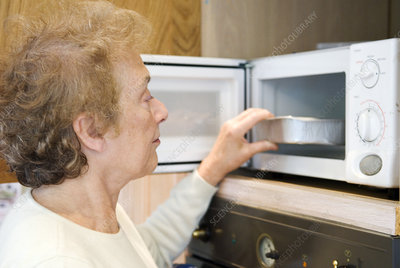 Elderly woman using a microwave oven