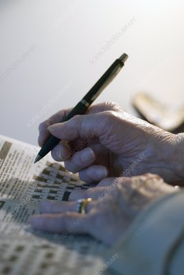 Elderly person doing a crossword