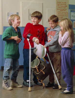 Handicapped boy with crutches and his friends
